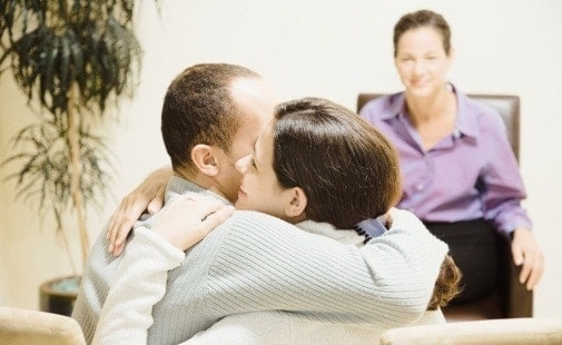 Multi-ethnic couple hugging at therapy session
